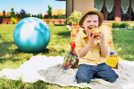 Charming kid eating huge apple photo