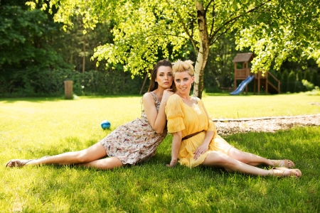 Two attractive ladies resting on the flower meadow photo