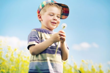 blowball: Laughing kid carrying blow-ball in his hands Stock Photo