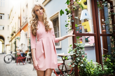 Tall and pretty young female model walking in old town photo