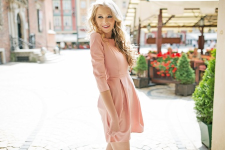 Ashamed blonde lady wearing pink dress photo