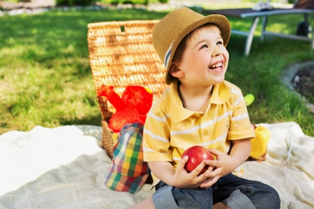 Smiling kid holding juicy apple photo