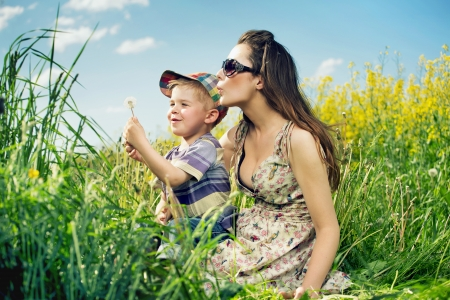 Happy family having a lot of fun with dandelions photo