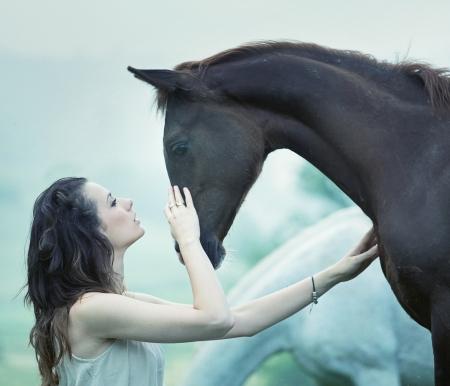 官能的な女の野生の馬をなでる