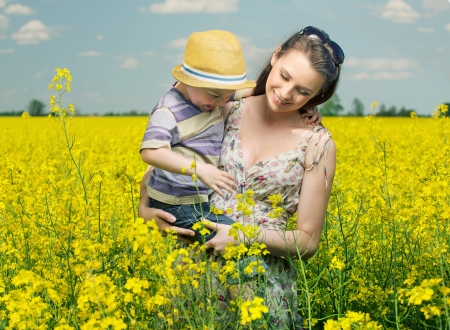 Mother and son walking among the canola flowers photo