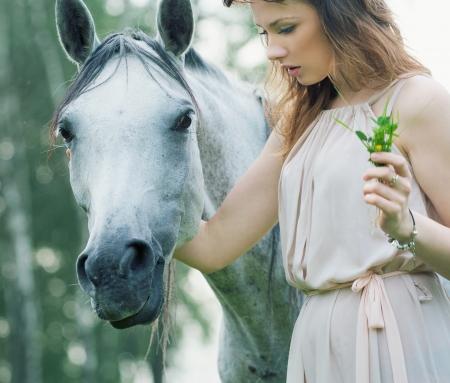 okşayarak: Genç bayan okşayarak atı gördü