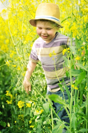 Smiling child running among the canola flowers photo