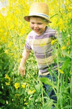 bright eyed: Smiling child running among the canola flowers