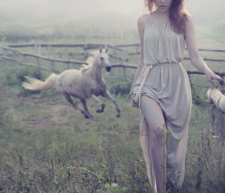 femme a cheval: Délicat dame brune posant avec le cheval en arrière-plan Banque d'images