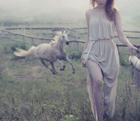 horses in field: Delicate brunette lady posing with horse in the background