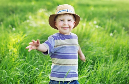 Portrait of a cute small kid playing  on the meadow photo
