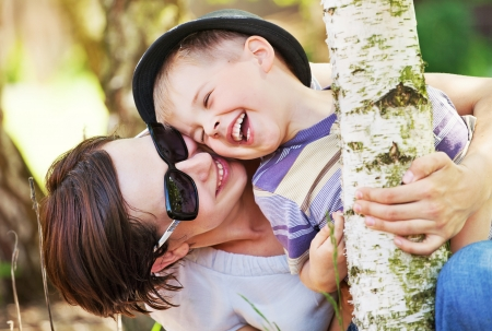 laughter: Laughing small boy hugged by his pretty mother Stock Photo