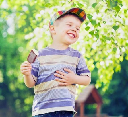 children: Довольный маленький ребенок ест мороженое Фото со стока