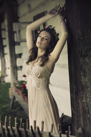 Sensual sexy lady posing next to the wooden house photo
