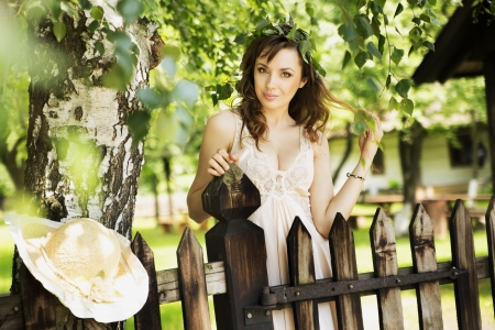 Sexy brunette woman leaning on the wooden fence