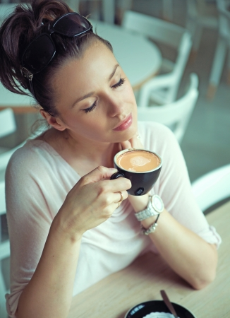 cote d'azure: Dreaming brunette woman with cup of coffee