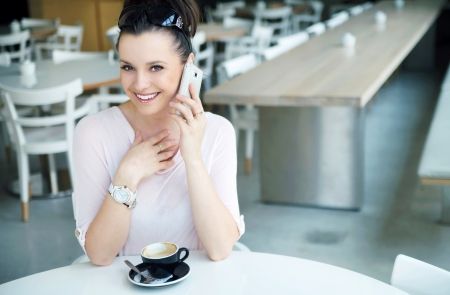 cote d'azure: Surprised brunette lady talking by the cell phone Stock Photo