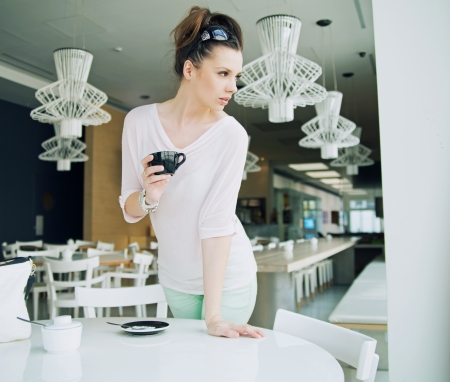cote d'azure: Alluring brunette lady holding a cup of coffee