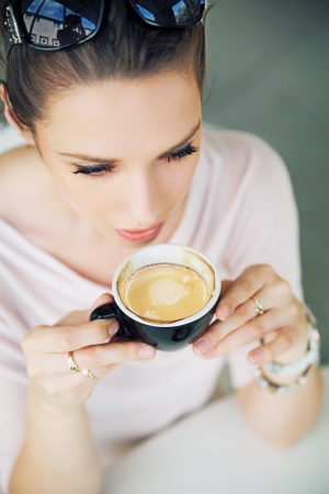 Attractive brunette woman taking a gulp of coffee Stock Photo - 21553332