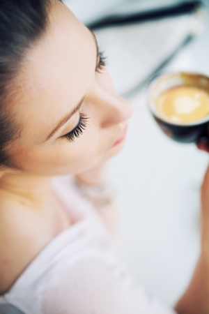 Nice picture of resting brunette lady holding a cup of coffee Stock Photo - 21553333