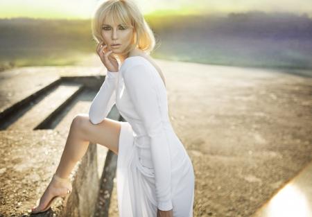 windblown: Beautiful blond lady in white dress Stock Photo