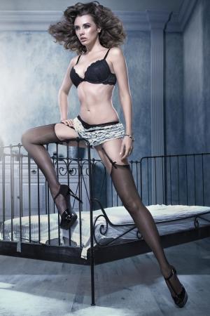 morena sexy: Sexy mujer morena apoy�ndose en marco de la cama