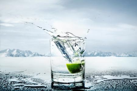 Kunstbeeld van citroen gegooid om het glas vol water Stockfoto