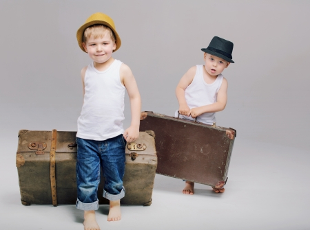 Brothers holding their really heavy luggages photo