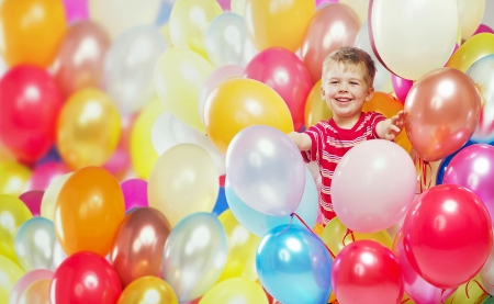 Laughing boy playing among the colorful baloons