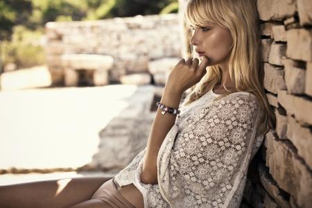moda: Riflessivo donna bionda leaing sul muro di pietra