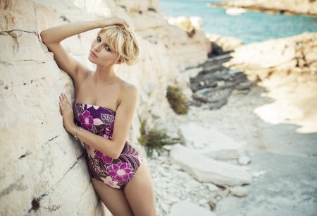 Blonde cute lady leaning on the bright rock photo