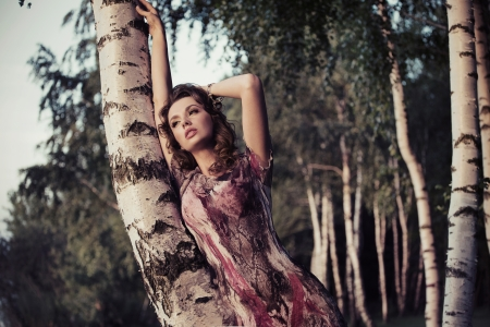 An attractive lady leaning on the birch