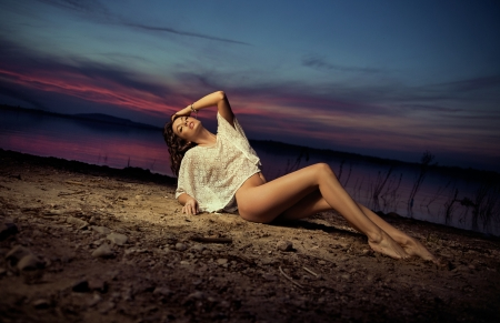 Sensual brunette lady lying on the ground photo