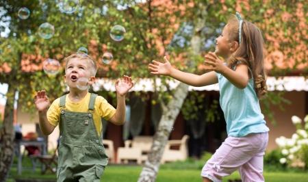 bambini che giocano: Bambini che giocano in giardino estivo Archivio Fotografico