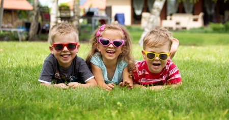 Happy laughing children lying on the grass