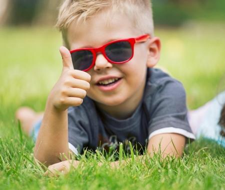 pequeño: Retrato de muchacho sonriente que muestra los pulgares para arriba gesto