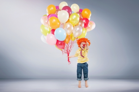 party balloons: Small jumping kid holding bunch of balloons Stock Photo