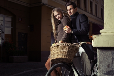 evening wear: Great young couple riding oldfashion bicycle