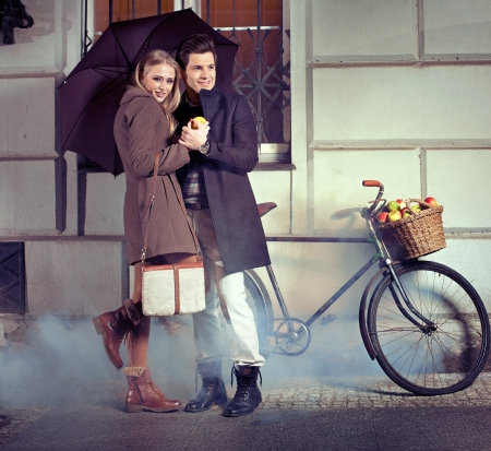 Smart couple with umbrella on rainy evening