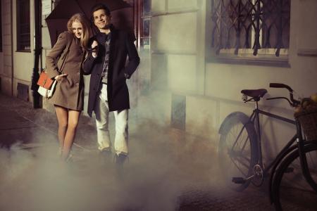 uomo sotto la pioggia: Eleganti giovani amici camminare sul marciapiede storico