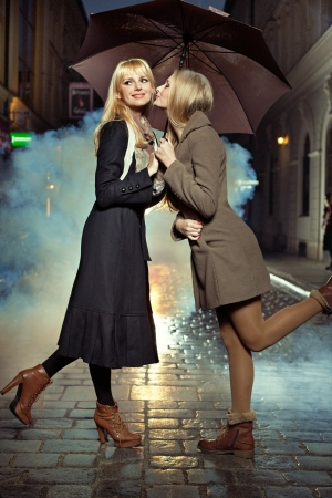 Blonde girl kissing her best friend's chick  photo