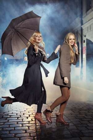 Two sexy blonde ladies running during rain photo