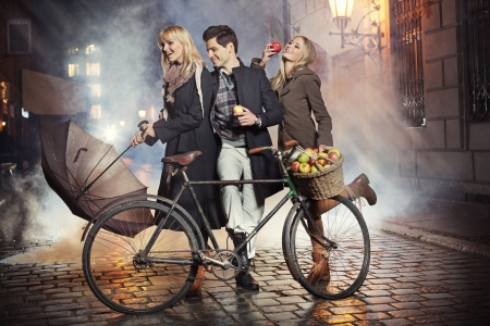 Three young friends, apples and bicycle
