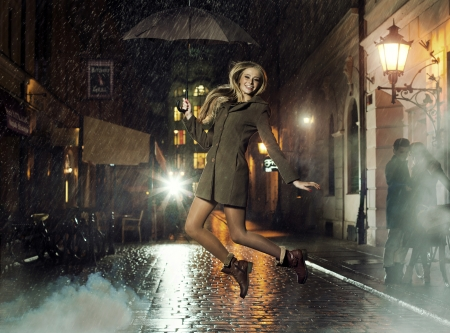 Fantastic photo of attractive lady jumping in heavy rain
