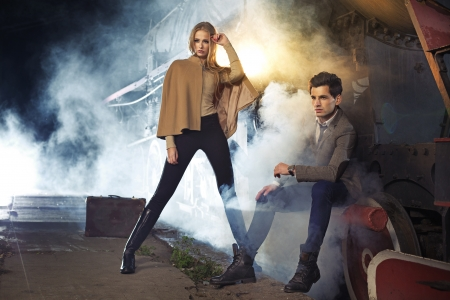 overcoat: Fashion photo of two models next to the engine