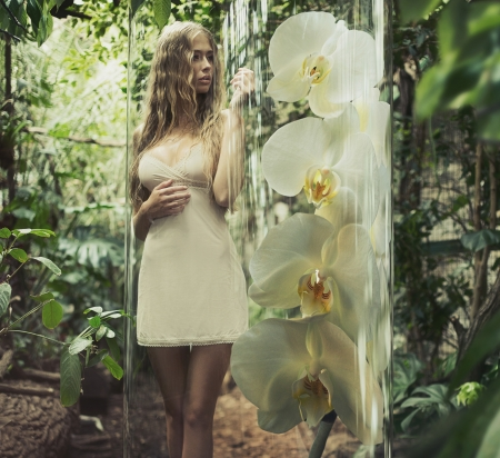 Blonde lady with curly hair among greenery photo
