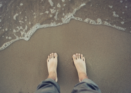 Photo of male bare foot near the sea water photo