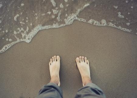 sea water: Photo of male bare foot near the sea water