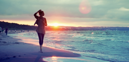 sunset sky: Alluring lady walking along the seaside Stock Photo