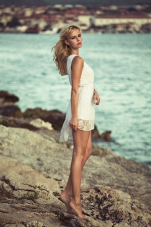 Blonde delicate woman on the rocks photo